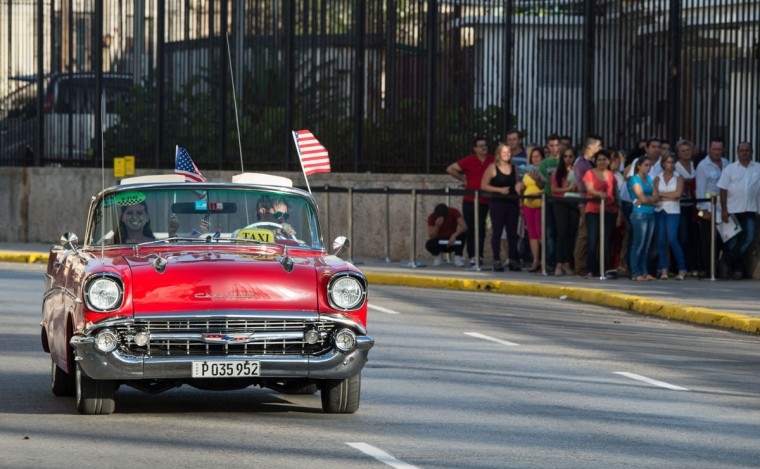A vintage car with US flags drives by the US embassy in Havana, on July 20, 2015. The United States and Cuba formally resumed diplomatic relations Monday, as the Cuban flag was raised at the US State Department in a historic gesture toward ending decades of hostility between the Cold war foes. (AFP Photo/P /adalberto )