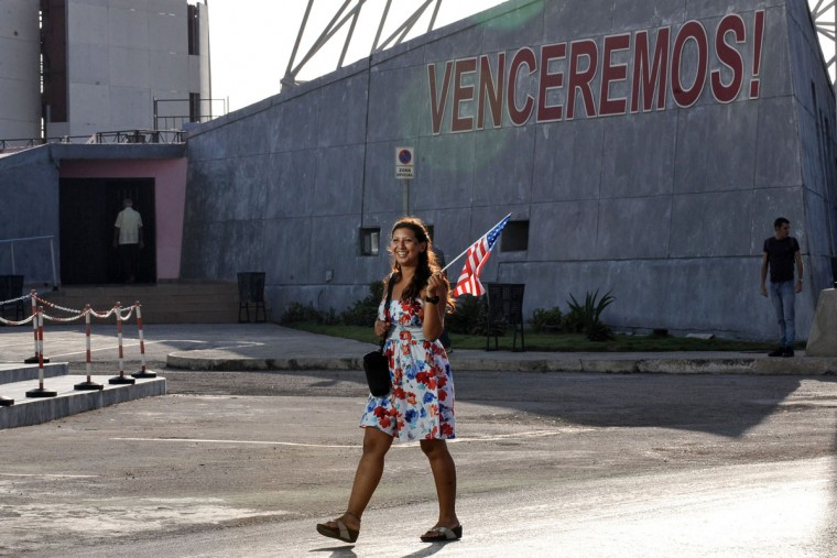 A woman carrying a US flag walks by the US embassy in Havana, on July 20, 2015. The United States and Cuba formally resumed diplomatic relations Monday, as the Cuban flag was raised at the US State Department in a historic gesture toward ending decades of hostility between the Cold war foes. (AFP Photo/P /yamil )