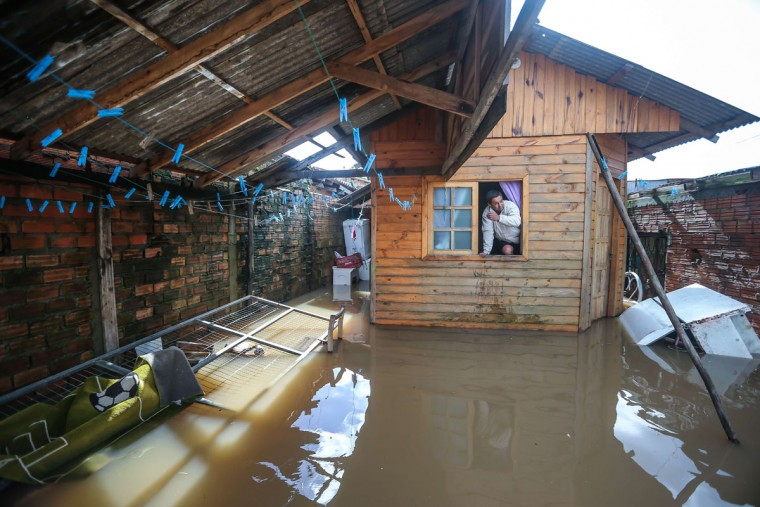 A local resident looks from inside his home at the flooded courtyard in Villa Rica, Gravatai, Brazil, on July 21, 2015. (JEFFERSON BERNARDES/AFP/Getty Images)