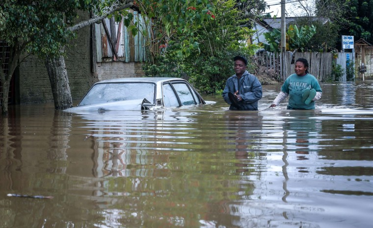 A couple wades through the streets of the flooded neighborhood of Vila Rica, in Gravatai, southern Brazil, on July 21, 2015. (JEFFERSON BERNARDES/AFP/Getty Images)