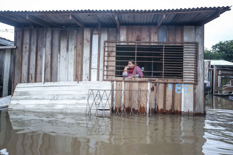 A woman looks through a window of her flooded house in Villa Rica, Gravatai, Brazil, on July 21, 2015. (JEFFERSON BERNARDES/AFP/Getty Images)