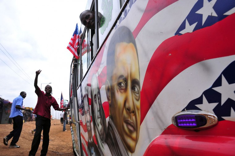 """Solomon Murimia, a """"matatu"""" minibus driver, gestures as he calls on clients beside his minibus with a painting depicting US Presidents Abraham Lincoln and Barack Obama and US scientist and statesman Benjamin Franklin on July 22, 2015 in Nairobi. Obama will make a first presidential pilgrimage to his father's homeland of Kenya later this month, the capstone of a weeklong overture to Africa taking in three key nations. (SIMON MAINA/AFP/Getty Images)"""