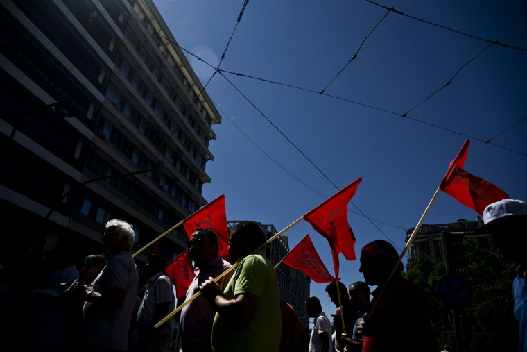 Demonstrators hold flags as they participate with hundreds of others in a demonstration called by the main Portuguese union CGTP-IN (General Confederation of the Portuguese Workers) to protest against anti-labor and anti-social policies of the Portuguese government in Lisbon on July 22, 2015. (PATRICIA DE MELO MOREIRA/AFP/Getty Images)