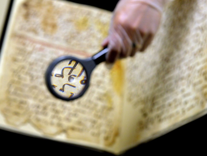 """Marie Sviergula, conservator of the University of Birmingham, holds a Koran manuscript in Birmingham England on July 22, 2015. A Koran manuscript has been carbon dated to close to the time of the Prophet Mohammed, making it one of the oldest in the world, a British university said today. The two leaves of parchment, filled with """"surprisingly legible"""" text from Islam's holy book, have been dated to around the early seventh century, the University said. (PAUL ELLIS/AFP/Getty Images)"""