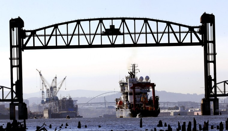 Royal Dutch Shell PLC icebreaker Fennica heads back to the Portland of Portland, at left, after it was blocked on its way to Alaska by activists hanging from the St. Johns bridge in Portland, Ore., Thursday, July 30, 2015. The icebreaker is a vital part of Shell's exploration and spill-response plan off Alaska's northwest coast. Environmental activists on St. Johns Bridge and kayakers on the Willamette River below have been blocking the icebreaker from heading to the Arctic for a drill operation. (AP Photo/Don Ryan)