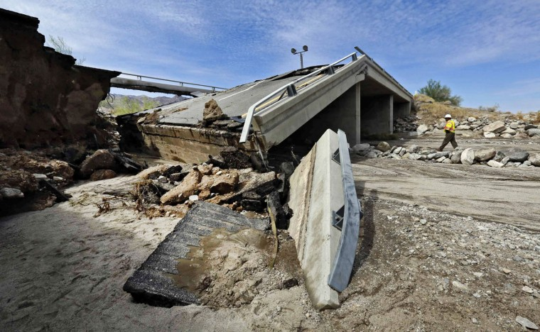 A worker walks near a washed-out bridge near the town of Desert Center, along Interstate 10 in Southern California, on Monday, July 20, 2015. All traffic along one of the major highways connecting California and Arizona was blocked indefinitely when the bridge over a desert wash collapsed during a major storm, and the roadway in the opposite direction sustained severe damage. (AP Photo/Nick Ut)