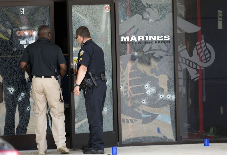Police officers enter the Armed Forces Career Center through a bullet-riddled door after a gunman opened fire on the building Thursday, July 16, 2015, in Chattanooga, Tenn. Authorities say there were multiple casualties including the gunman. (AP Photo/John Bazemore)