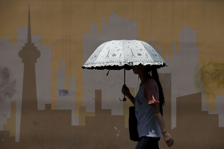 A woman carrying an umbrella to shield from the sun as she walks past a mural of a city skyscrapers in Beijing Monday, July 13, 2015. The National Meteorological Center (NMC) has issued a yellow alert for high temperatures as China is entering the height of summer. A heat wave will hit central, eastern and northern China on Monday with temperatures in some regions rising to around 40 degrees Celsius (104 degrees Fahrenheit) , Chinese state media reported. (AP Photo/Andy Wong)