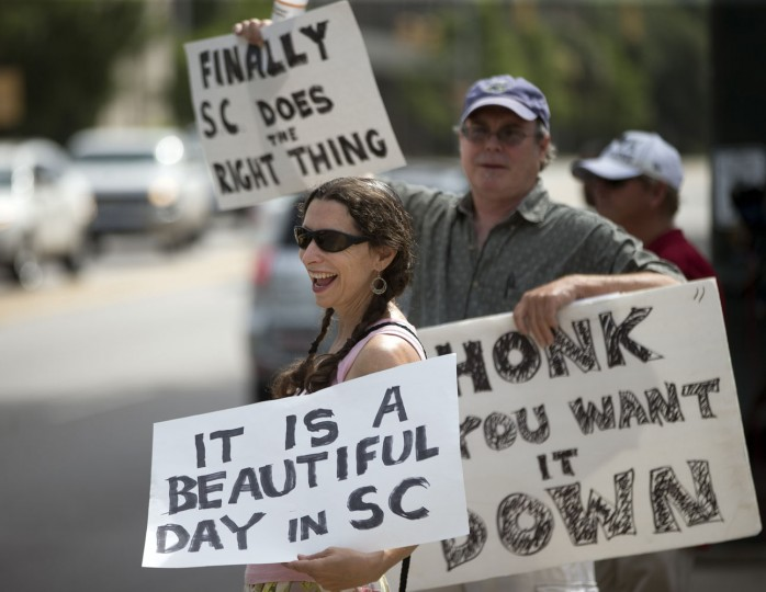 Leslie Minerd, of Columbia, S.C., holds a sign as she celebrates outside the South Carolina Statehouse, Thursday, July 9, 2015, in Columbia, S.C. More than 50 years after South Carolina raised a Confederate flag at its Statehouse to protest the civil rights movement, the rebel banner will be removed Friday in a state where such a reversal seemed unthinkable a month ago. (AP Photo/John Bazemore)