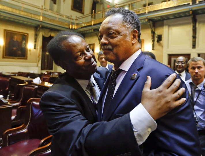Rep. Carl Anderson, D-Georgetown, left, embraces Rev. Jesse Jackson after the House approved a bill removing the Confederate flag from the Capitol grounds early Thursday, July 9, 2015, in Columbia, S.C. (AP Photo/John Bazemore)