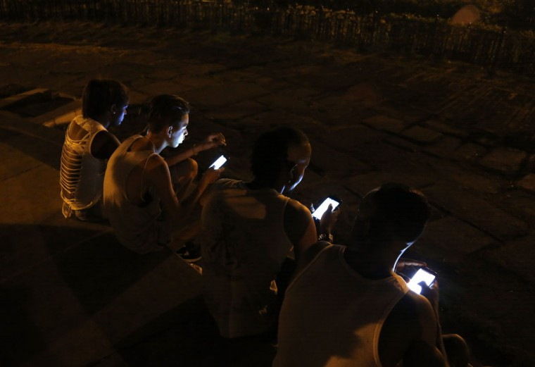 Youth use their smartphones to surf the Internet, using a password protected wifi network coming from a five star hotel in downtown Havana, Cuba, late Wednesday, July 1, 2015. (AP Photo/Desmond Boylan)