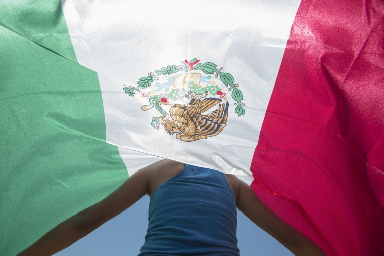 Kimberly Esparza walks draped in a Mexican flag during a protest against presidential candidate Donald Trump, Thursday, July 23, 2015, at Laredo International Airport in Laredo, Texas. (AP Photo/Darren Abate)