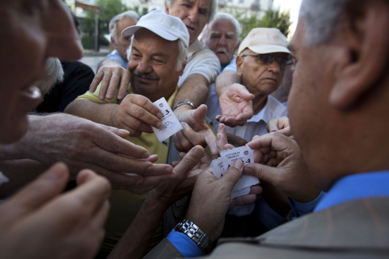 A bank employee distributes tags with queue positions to pensioners as they wait outside the main gate of the national bank of Greece to withdraw a maximum of 120 euros ($134) in central Athens, Thursday, July 16, 2015. Greeceís troubled left-wing government is seeking urgent relief from European lenders on Thursday, after it pushed a harsh austerity package thought parliament, triggering a revolt in the ruling party and violent demonstrations in central Athens. (AP Photo/Emilio Morenatti)