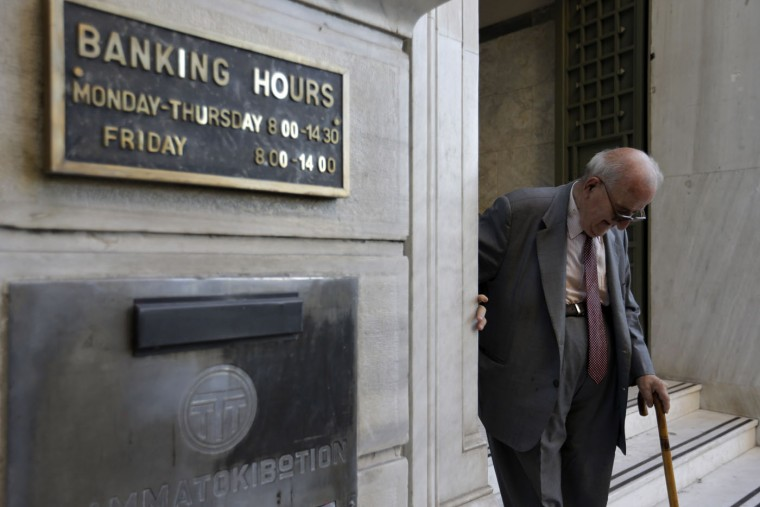 An elderly man leaves a branch of the National Bank of Greece in Athens, Monday, July 20, 2015. Greek banks reopen on Monday morning, but many restrictions on transactions, including cash withdrawals, will remain. Also, many goods and services will become more expensive as a result of a rise in Value Added Tax approved by Parliament last Thursday, among the first batch of austerity measures demanded by Greece's creditors. (AP Photo/Thanassis Stavrakis)