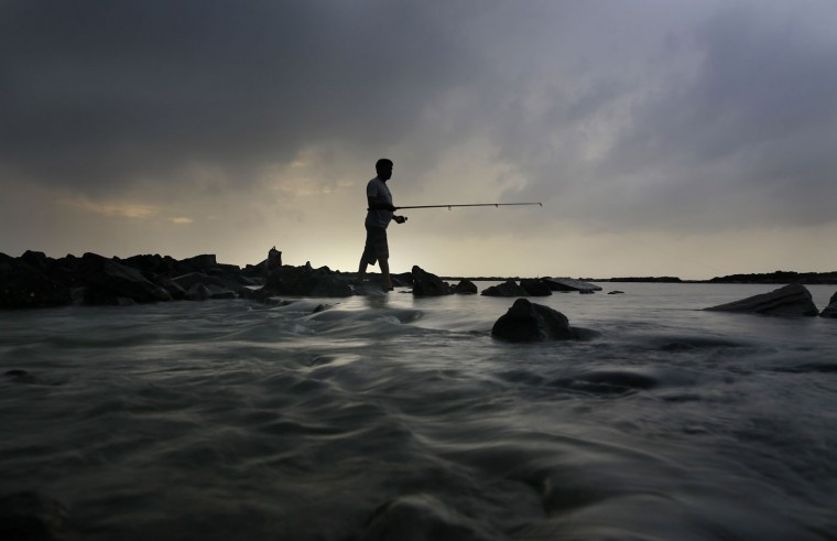 An Indian man tries to catch fish along the shores of the Arabian sea in Mumbai, Maharashtra state, India, Thursday, July 23, 2015. After prolong dry spell, monsoon rains, crucial for India's agriculture, returned to the city bringing relief from warm and humid weather. (AP Photo/Rafiq Maqbool)