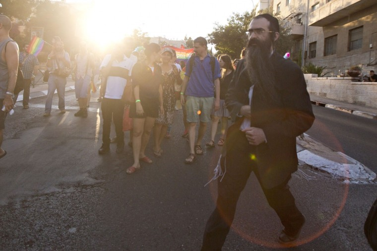 Ultra-Orthodox Jew Yishai Schlissel walks through a Gay Pride parade and is just about to pull a knife from under his coat and start stabbing people in Jerusalem Thursday, July 30, 2015. Schlissel was recently released from prison after serving a term for stabbing several people at a gay pride parade in 2005, a police spokeswoman said.(AP Photo/Sebastian Scheiner)