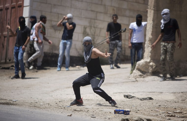 A Palestinian uses a slingshot towards Israeli soldiers during clashes after the funeral of Falah Abu Maria in the village of Beit Omar near the West Bank city of Hebron, Thursday, July 23, 2015. A Palestinian man was killed Thursday morning during a clash between Palestinians and Israeli troops in the West Bank, a Palestinian hospital official and the Israeli army said. Maria was killed by three live bullets shot at his chest at close range, said Yousef Takrouri, deputy director of Al-Ahli Hospital in the West Bank city of Hebron. (AP Photo/Majdi Mohammed)