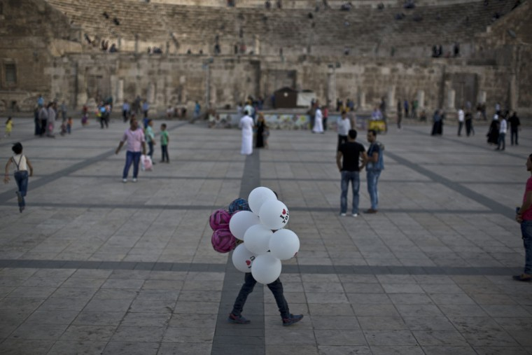 A Jordanian boy looks for customers to sell his balloons, at an ancient Roman theater in Amman, Jordan, Friday, July 24, 2015. (AP Photo/Muhammed Muheisen)