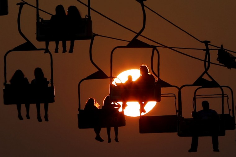 The sun sets behind people hanging from a ride at the State Fair Meadowlands, Wednesday, July 1, 2015, in East Rutherford, N.J. The fair closes on Sunday. (AP Photo/Julio Cortez)