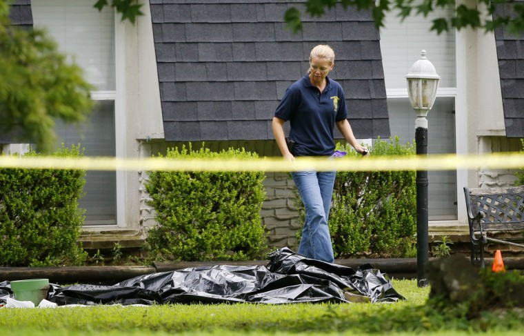 An investigator walks past a tarp covering a body in the front yard of a house in Broken Arrow, Okla., Thursday, July 23, 2015, where five family members were discovered stabbed to death. Police were questioning two teenage brothers in connection with the deaths of their parents and three younger siblings. A 2-year-old sister was found unharmed. (AP Photo/Sue Ogrocki)