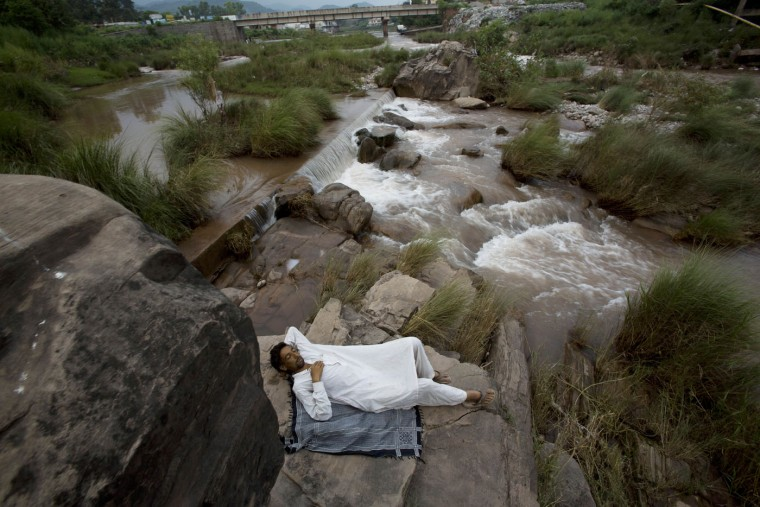 A Pakistani man takes a nap at waterside during a hot afternoon in Islamabad, Pakistan, July 30, 2015. (AP Photo/B.K. Bangash)