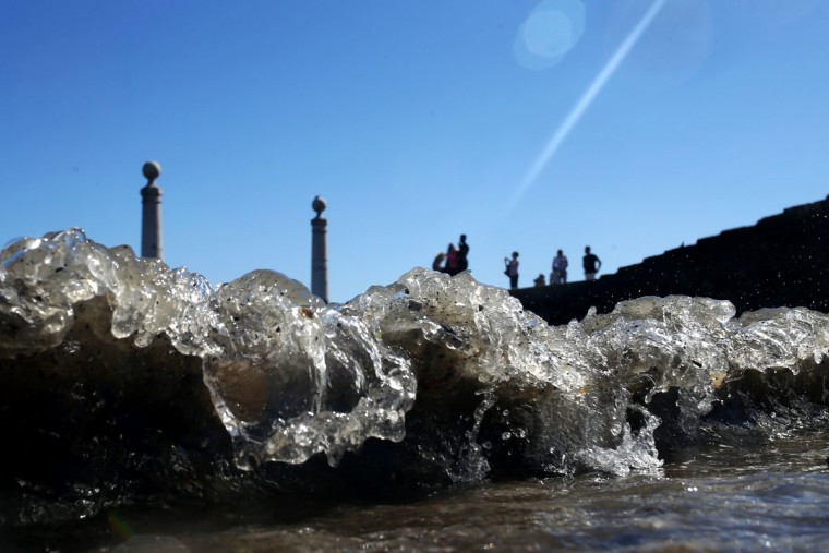 Small waves break as people take photographs at the Cais das Colunas dock by the Tagus riverbank, in Lisbon, Saturday, July 11, 2015. The place is a popular location for locals and tourists to pause, relax or take photographs. (AP Photo/Francisco Seco)