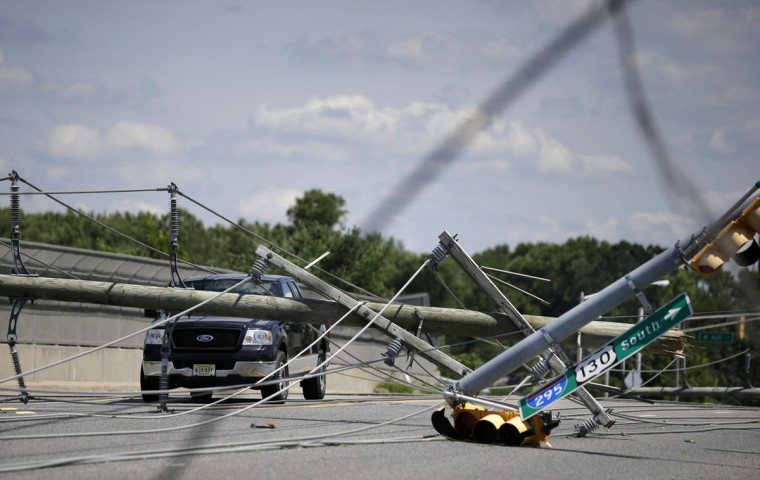 A truck is abandoned amid downed electrical poles and wires Wednesday, June 24, 2015, after a violent storm passed the area Tuesday night in Gibbstown, N.J. Gloucester, Camden, Burlington and Salem counties saw the most damage from the ferocious storms that barreled through the region Tuesday night. (AP Photo/Mel Evans)