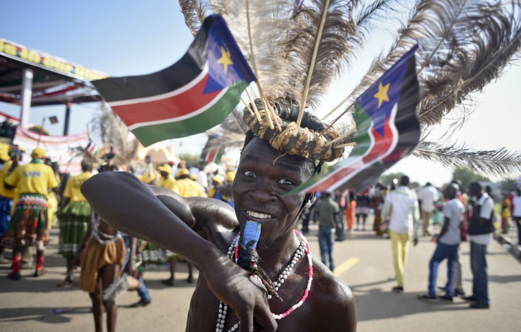 A South Sudanese man wears a headdress of feathers and the national flag, as he attends an independence day ceremony in the capital Juba, South Sudan, Thursday, July 9, 2015. South Sudan marked four years of independence from Sudan on Thursday, but the celebrations were tempered by concerns about ongoing violence and the threat of famine. (AP Photo/Jason Patinkin)