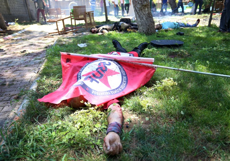 Bodies lie on the ground with one being covered with a Federation of the Socialist Youth Associations flag, after an explosion, in the southeastern Turkish city of Suruc near the Syrian border, Turkey, Monday, July 20, 2015. An explosion Monday killed at least 10 people and injured scores of others in the southeastern Turkish city of Suruc near the Syrian border, state-run Turkish news agencies reported. The private Turkish DHA news agency said at least 50 people had been hospitalized in the midday explosion. There was no immediate claim of responsibility for the blast. (AP Photo/Ozcan Soysal)