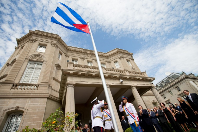Cuban Foreign Minister Bruno Rodriguez, right of center, applauds with other dignitaries after raising the Cuban flag over their new embassy in Washington, Monday, July 20, 2015. Cuba's blue, red and white-starred flag was hoisted Monday at the country's embassy in Washington in a symbolic move signaling the start of a new post-Cold War era in U.S.-Cuba relations. (AP Photo/Andrew Harnik, Pool)