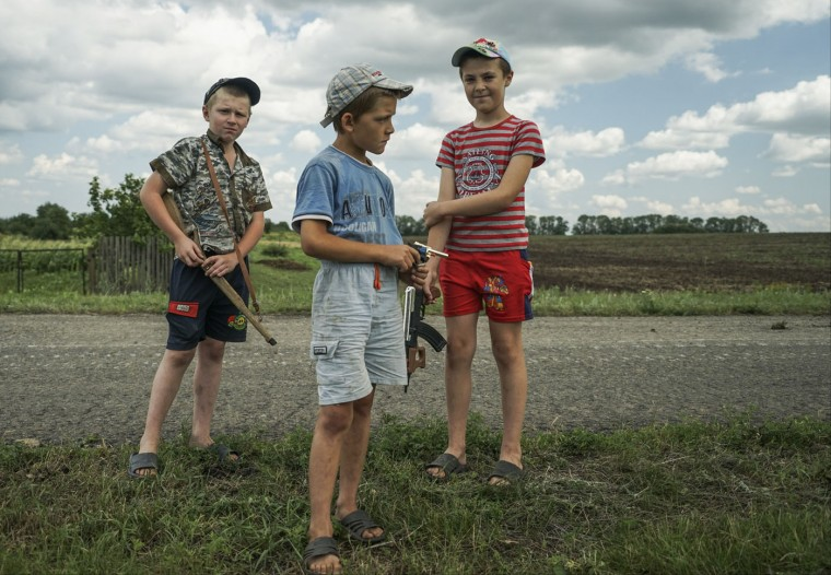 Local children holding toy guns stand at the site of the crashed Malaysia Airlines Flight 17 plane, near the village of Hrabove, eastern Ukraine, Thursday, July 16, 2015. A year since a Malaysia Airlines Boeing 777 was blown out of the sky over war-ravaged eastern Ukraine, killing 298 people, there has been little official word of progress in determining what brought down Flight MH17. (AP Photo/Mstyslav Chernov)