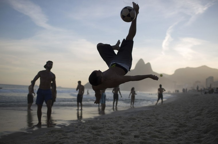 "A beachgoer bicycle kicks the ball during a game of ""altinho"" along the shore of Ipanema Beach in Rio de Janeiro, Brazil, Monday, July 13, 2015. Altinho is a popular local game that is played with a soccer ball on the beach. The goal is not to let the ball drop, but passing to other players while keeping it airborne. (AP Photo/Leo Correa)"