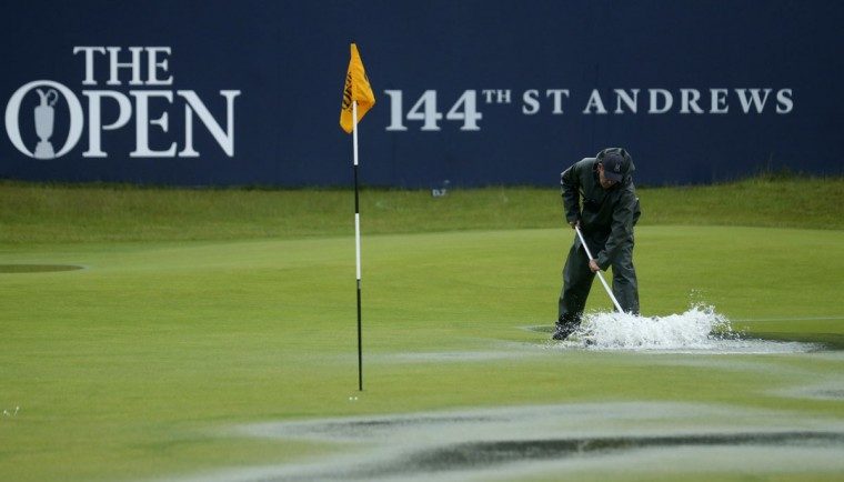 A groundskeeper uses rollers to clear excess water after play was delayed by rain during the second round of the British Open Golf Championship at the Old Course, St. Andrews, Scotland, Friday, July 17, 2015. (AP Photo/Peter Morrison)