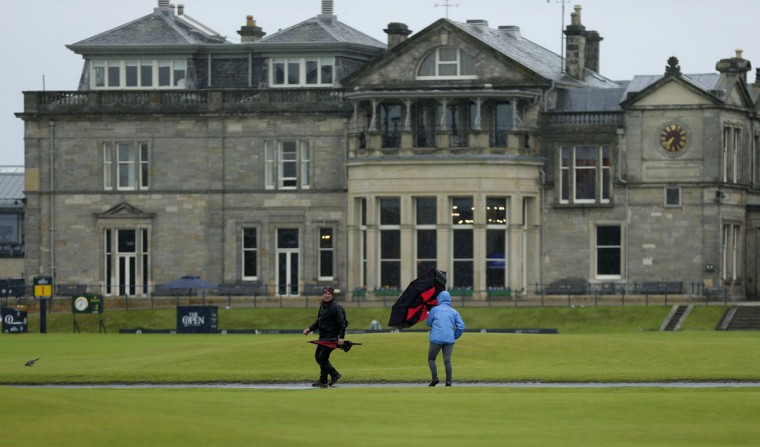 People walk through the rain and wind as play is suspended during the second round of the British Open Golf Championship at the Old Course, St. Andrews, Scotland, Friday, July 17, 2015. (AP Photo/David J. Phillip)