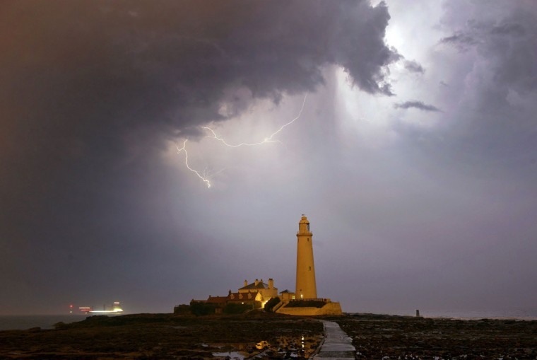 Lightning flashes in the sky above the lighthouse near Blyth on the Northumberland coast early Thursday July 2, 2015 as thunderstorms and showers ushered in some cooler weather following the record breaking temperatures of Wednesday. (Owen Humphreys/PA via AP)