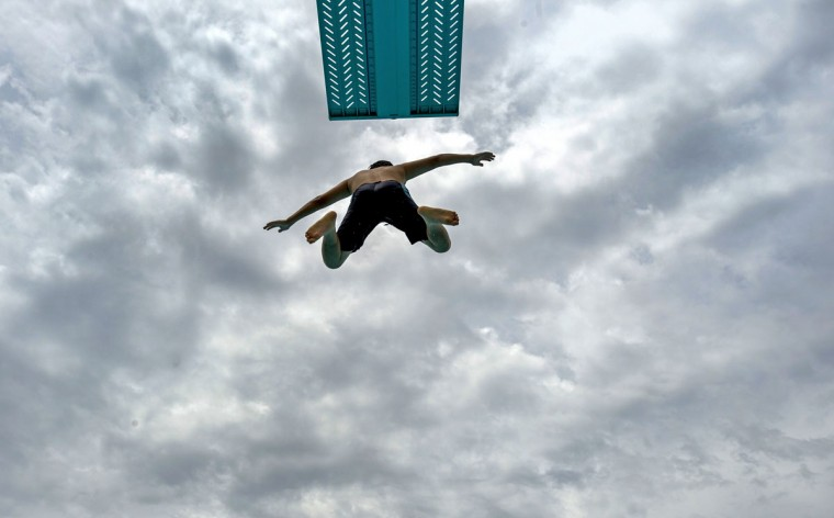 A youngster leaps off the diving board as the tries to stay cool at the William Peak Park pool in Buena Park, Calif., Wednesday, July 1, 2015. (Michael Goulding/The Orange County Register via AP)