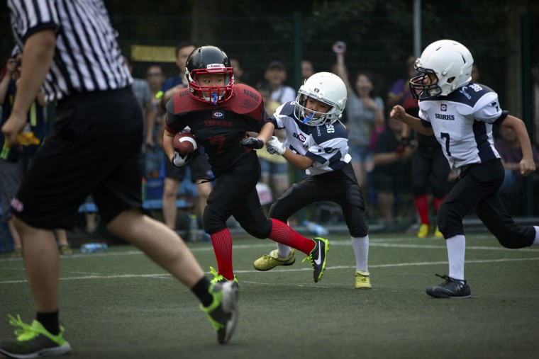 Zhang Qianyi, 9, left, of the Vipers team dodges a tackle of Zhao Yuxiang, 8, center, and Liu Jiayou, 9, right, of the Sharks during their American football game in Beijing. Chinaís capital might seem like an unlikely place to find American football, but interest among Chinese youth is growing. (AP Photo/Mark Schiefelbein)
