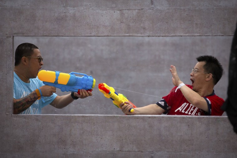 Players fire their water guns in a battle maze in Beijing, Saturday, July 4, 2015. Each player in the game aims to soak their opponents with water in the large outdoor maze, which organizers said was inspired by the online and mobile video games that are increasingly popular with China's youth. (AP Photo/Mark Schiefelbein)