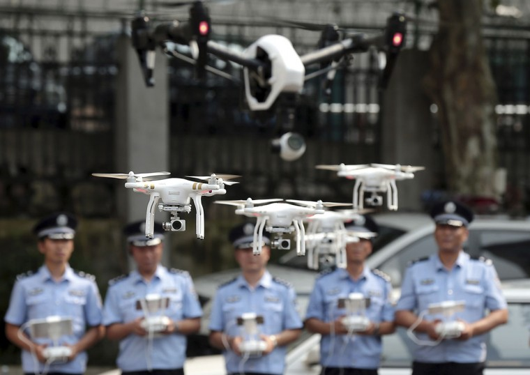 Chinese policemen practice controlling drones after a ceremony to mark the establishment of the first police drone squad in Nanjing in eastern China's Jiangsu province Tuesday July 14, 2015. The initial team of six officers and seven drones will take part in scouting, monitoring and emergency rescue operations. (Chinatopix Via AP)