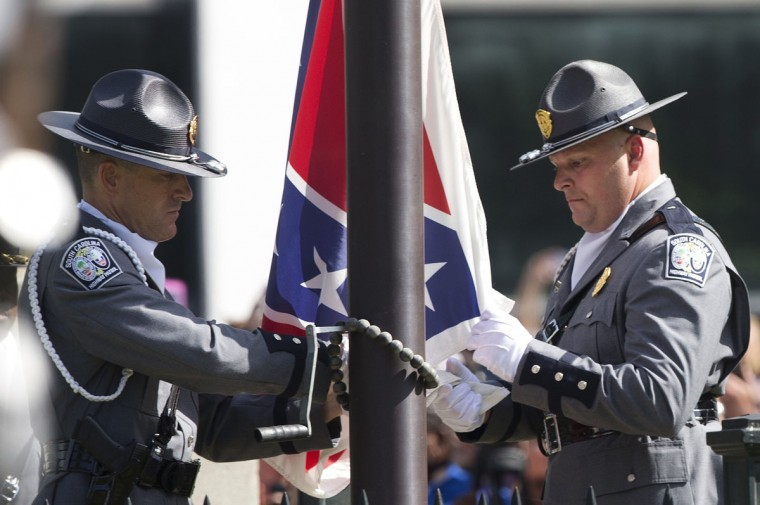 An honor guard from the South Carolina Highway patrol lowers the Confederate battle flag as it is removed from the Capitol grounds Friday, July 10, 2015, in Columbia, S.C. The Confederate flag was lowered from the grounds of the South Carolina Statehouse to the cheers of thousands on Friday, ending its 54-year presence there and marking a stunning political reversal in a state where many thought the rebel banner would fly indefinitely. (AP Photo/John Bazemore)