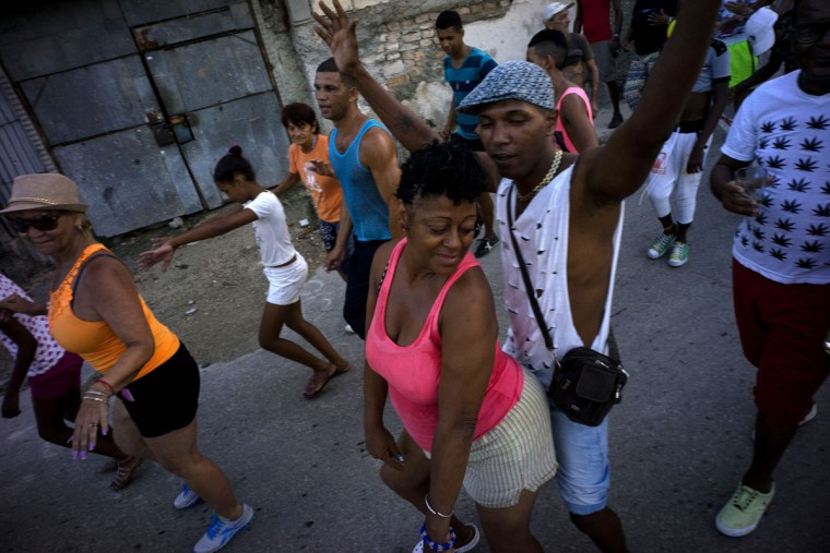 People sing and dance to the beat of drums at the break of dawn during a small fair in the Casablanca neighborhood of Havana, Cuba, Thursday, July 16, 2015. Casablanca residents have brought back lost traditions to their 420-year-old neighborhood, including this early morning parade that announces the start of the new day. (AP Photo/Ramon Espinosa)