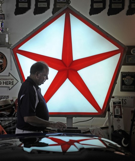 In this July 14, 2015 photo, Dave Jones walks in front of a Dodge car logo in his garage in New Palestine, Ind. The long time car collector has owned more than 200 cars in his life. (Tom Russo/Daily Reporter via AP)