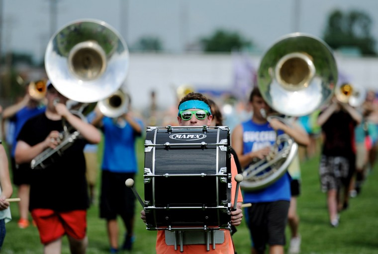 Bass drummer Elijah Price, center, works on marching fundamentals while carrying his instrument on the field during Henderson County High School's band camp at North Middle School in Henderson, Ky. Tuesday morning, July 14, 2015. (Darrin Phegley/The Gleaner via AP)