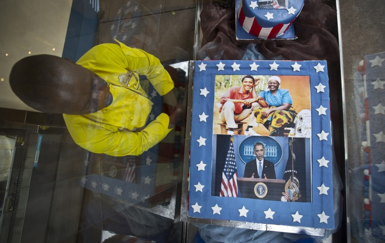 "Pastry Chef Svein Ochieng looks at the mock cakes he created featuring photographs of President Barack Obama and his step-grandmother Sarah Obama, and the message ""Welcome Home Sir..."", in a glass display case outside the Cafe Deli coffee shop, which a manager said Obama visited many years ago before he was a public figure, in Nairobi, Kenya Wednesday, July 22, 2015. In his first trip to Kenya since he was a U.S. senator in 2006, Obama is scheduled to arrive in Kenya on Friday, the first stop on his two-nation African tour in which he will also visit Ethiopia. (AP Photo/Ben Curtis)"