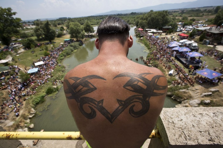 Spectators watch as winning diver Florit Gashi prepares to launch himself from the Ura e Shenjte bridge during the traditional annual high diving competition, near the town of Gjakova, 100 kms south of Kosovo capital Pristina on Sunday, July 26, 2015. (AP Photo/Visar Kryeziu)