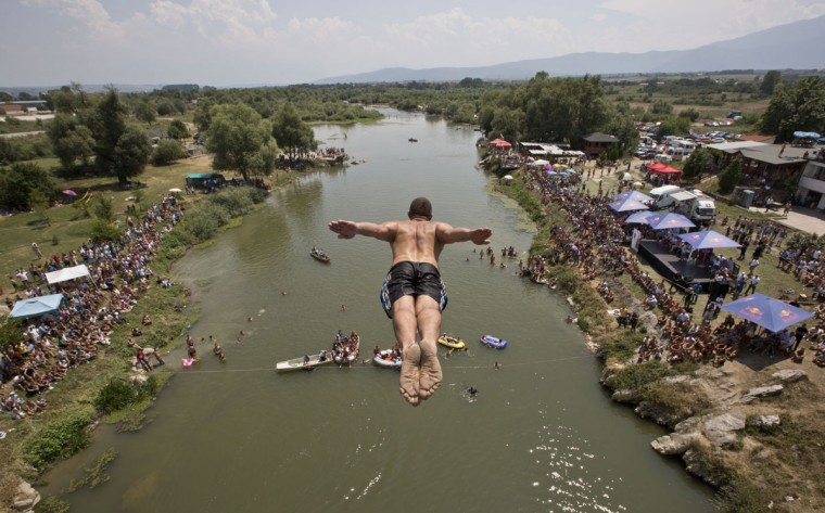 Spectators watch as a diver jumps from the Ura e Shenjte bridge during the traditional annual high diving competition, near the town of Gjakova, 100 kms south of Kosovo capital Pristina, Sunday, July 26, 2015. (AP Photo/Visar