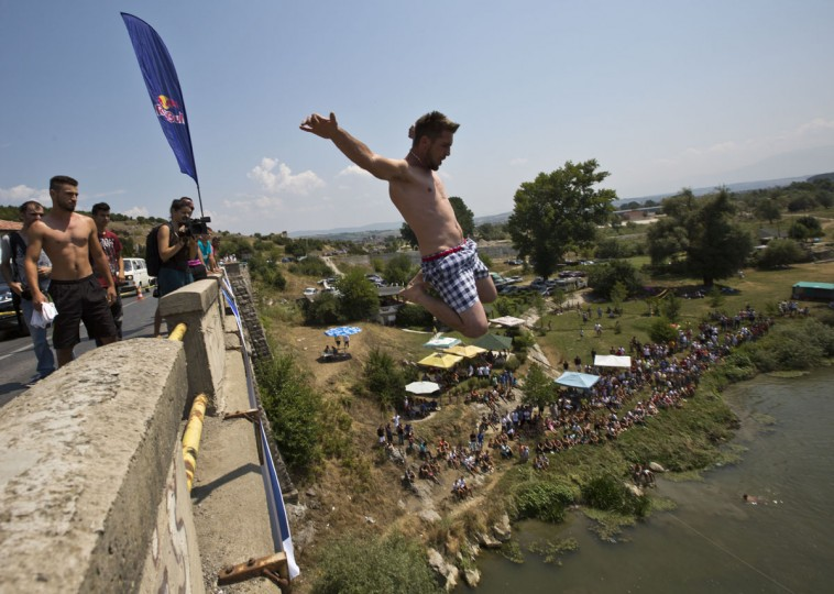 Spectators watch as a diver jumps from the Ura e Shenjte bridge during the traditional annual high diving competition, near the town of Gjakova, 100 kms south of Kosovo capital Pristina, Sunday, July 26, 2015. (AP Photo/Visar Kryeziu)