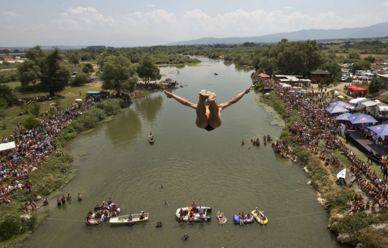 Spectators watch as a diver jumps from the Ura e Shenjte bridge during the traditional annual high diving competition, near the town of Gjakova, 100 kms south of Kosovo capital Pristina, Sunday, July 26, 2015. (AP Photo/Visar Kryeziu))