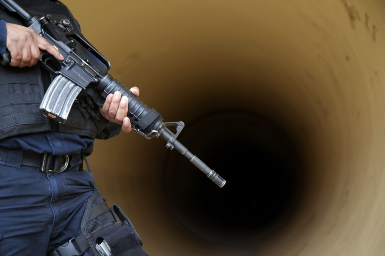 "A Federal police inspects a drainage pipe outside the Altiplano maximum security prison in Almoloya, west of Mexico City, Sunday, July 12, 2015. Mexico's most powerful drug lord, Joaquin ""El Chapo"" Guzman, escaped from a maximum security prison through a tunnel that opened into the shower area of his cell, the country's top security official announced. (AP Photo/Marco Ugarte)"