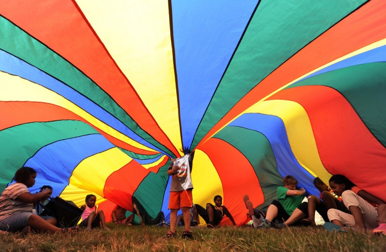 Children play under a parachute Wednesday, July 29, 2015, during the Summer Brain Gain Celebration, a community health fair held at the Boys & Girls Club of Benton Harbor, in Benton Harbor, Mich. (Don Campbell/The Herald-Palladium via AP)
